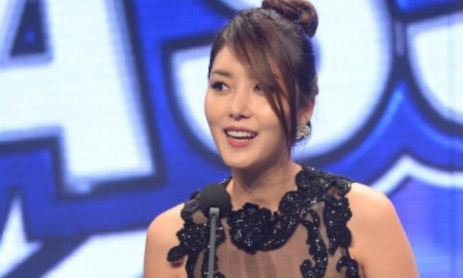 韩国女星李秀晶身穿黑色绣花美裙亮相颁奖活动,台上鞠躬显亲切