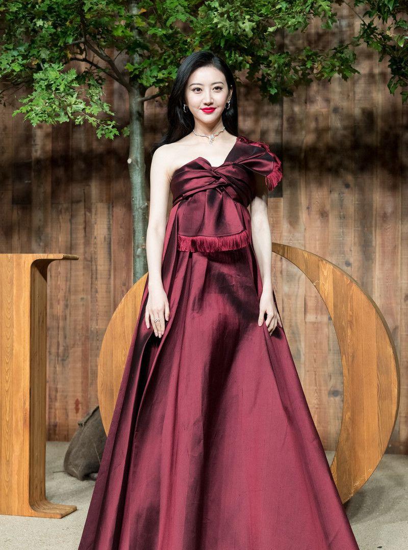 女演员景甜现身发布会,穿紫红色斜肩礼服,留长发优雅动人