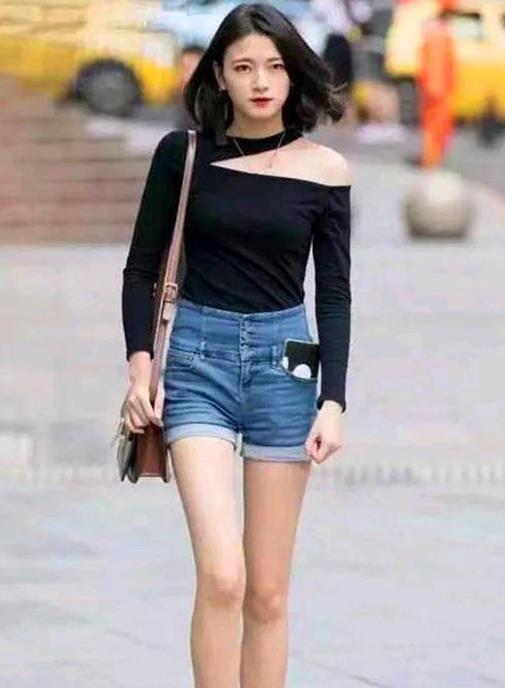 街拍:皮肤白皙的美女,一件黑色斜肩上衣配牛仔短裤,时尚气质