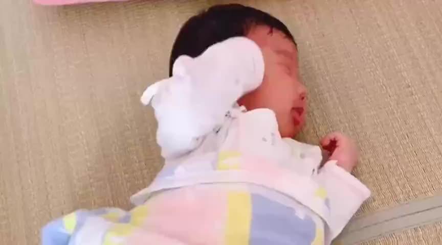 小宝宝躺在床上扭来扭去的,突然吐奶了,接下来的模样真让人心疼