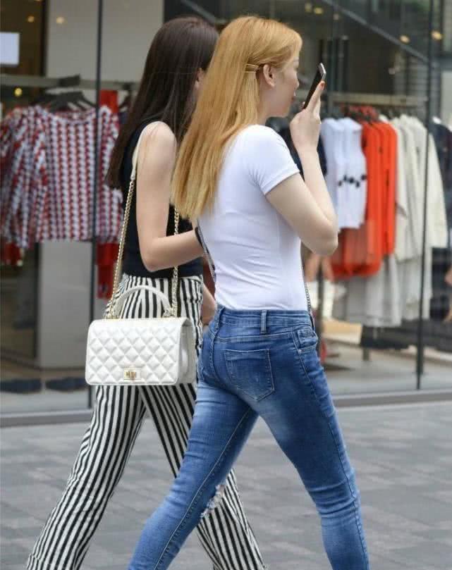 街拍美女:牛仔裤提高了腰线,小姐姐穿起来显腿瘦更显秀气