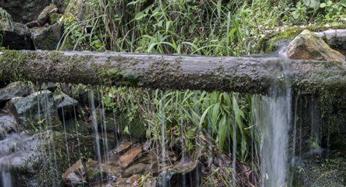 没有竹子的地方就把木头开槽,然后连接引水,尽头处是一口大缸,有石缸