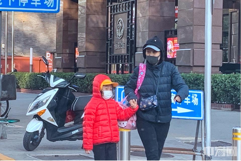 大风寒潮双预警 北京街头行人厚装顶风前行