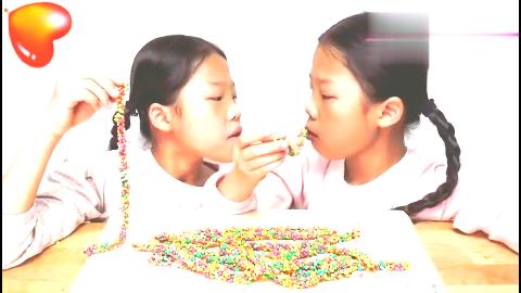 双胞胎姐妹把彩色糖果串成项链,好开心!