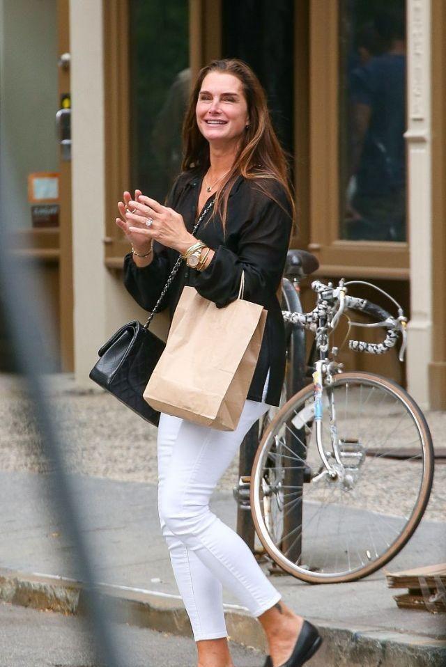 美国女模特现身街头,穿黑色衬衣白色休闲裤,做鬼脸心情大好