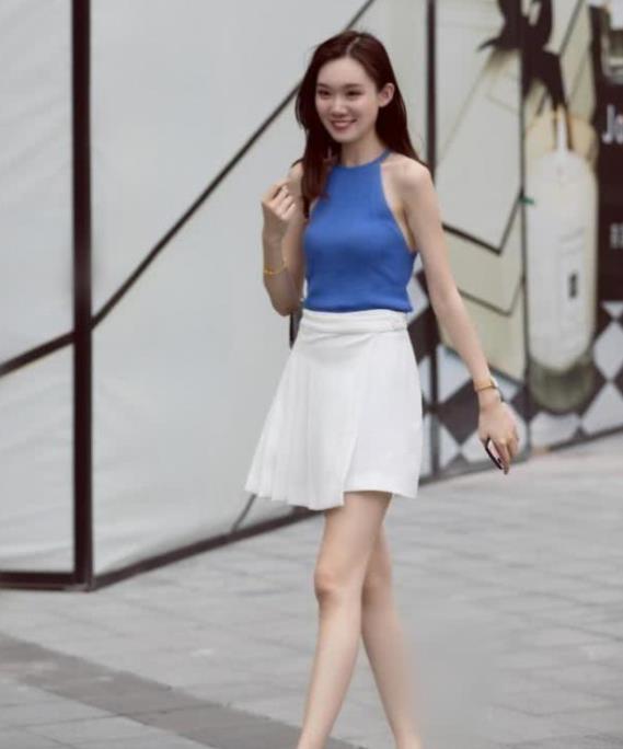 街拍:面带微笑的美女,一件蓝色背心配白色短裙,时尚魅力女神范