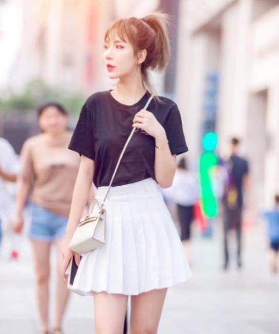 街拍:皮肤白皙的美女,一件黑色上衣配白色百褶裙,青春靓丽气息