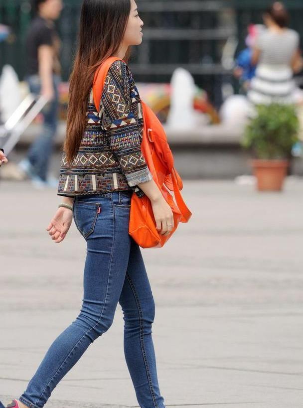 路人街拍:长发飘飘的牛仔裤美女,民族风上衣有点显老啊!