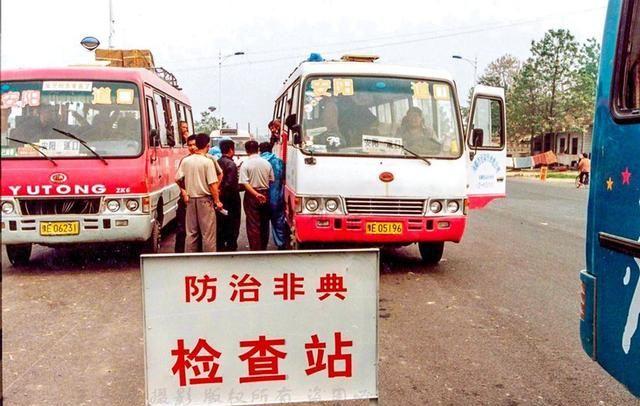 2003年老照片:抗击非典,防疫人员在长途客车上登记检查旅客
