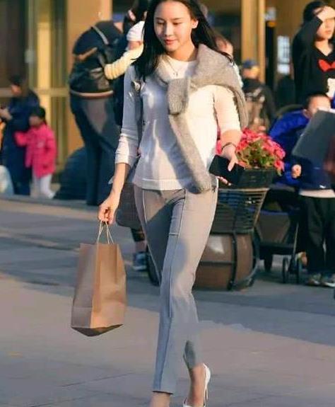 街拍:柔情绰态的美女,一件白色上衣配灰色裤子,时尚女性气质