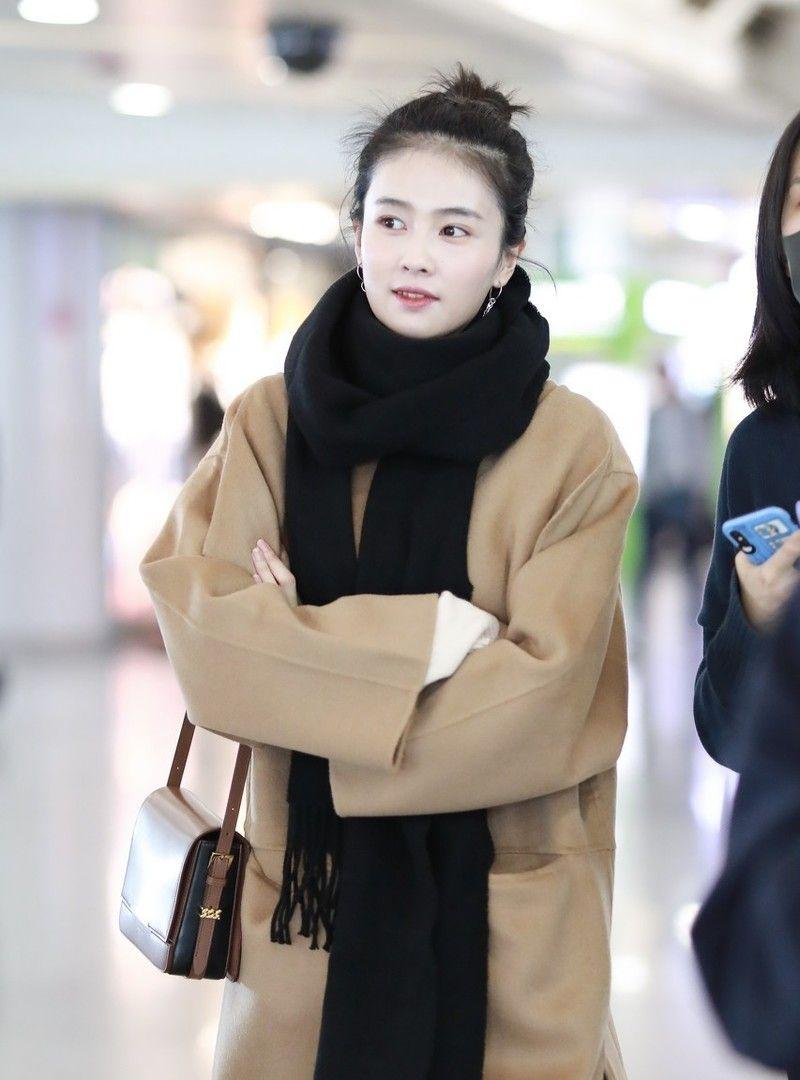 内地某女演员现身机场,穿驼色大衣时尚感十足,对镜比心甜笑