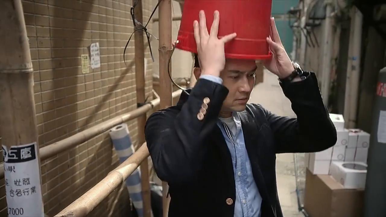 张智霖头上罩着一个水桶,把他淋成了一个落汤鸡