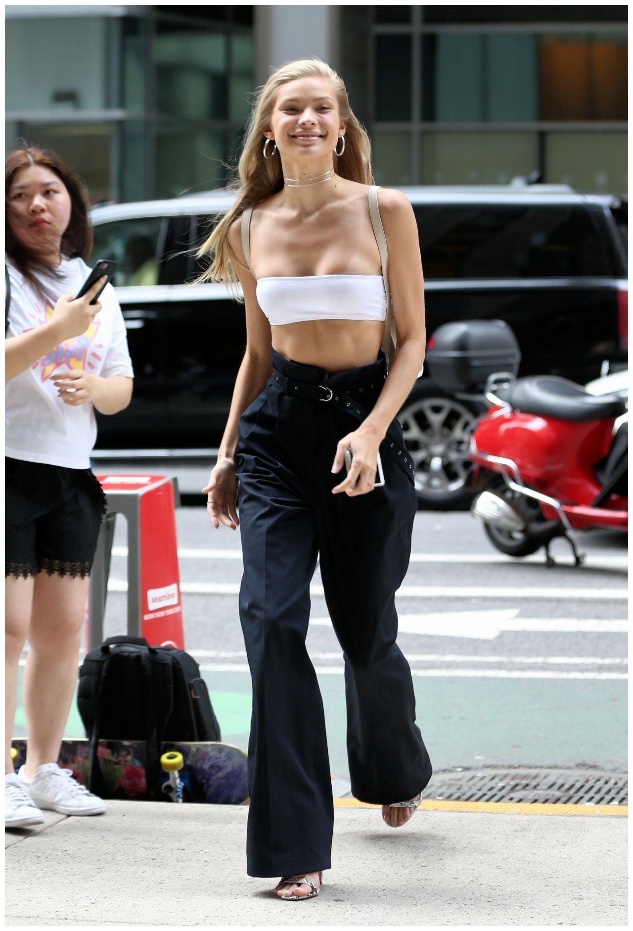 歌手女星身穿白色抹胸搭配黑色长裤时尚感足,对镜头献飞吻显俏皮