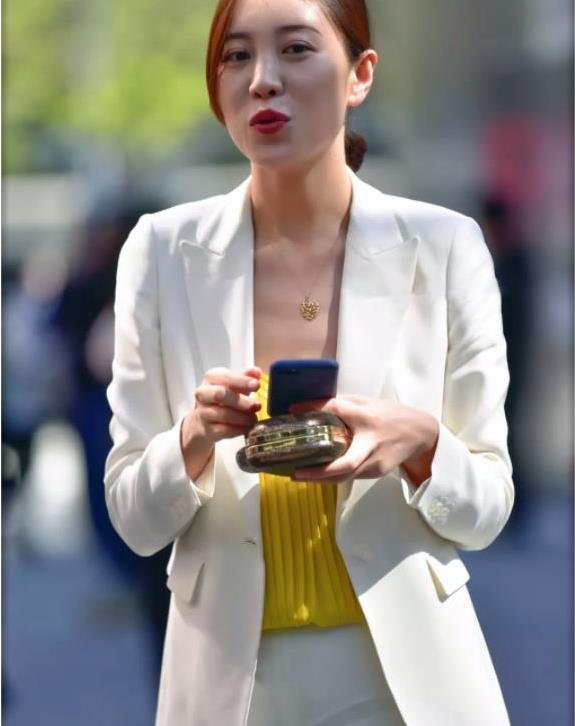 街拍:一位俏丽气质女白领,黄色吊带打底,白西装更显知性美