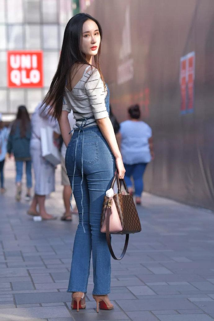 穿牛仔背带裤的美女,这回眸一笑很迷人哦。