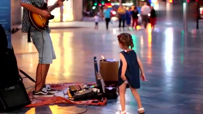 小女孩遇上街头卖唱歌手,立马上前伴舞,瞬间成最佳默契组合