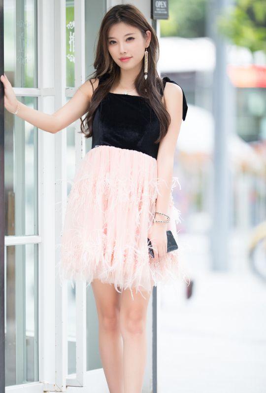 街拍:美女穿低胸吊带裙,凸显诱人上围,皮肤白皙,十分的养眼!