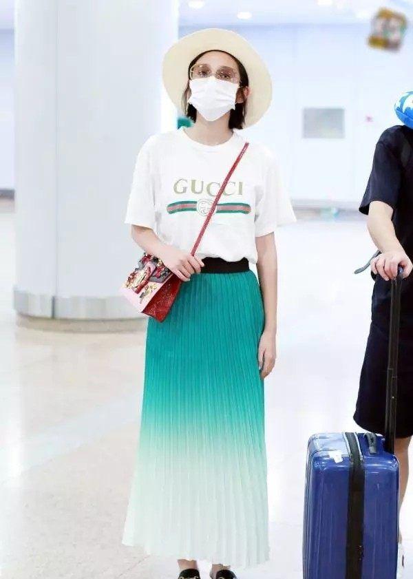 唐艺昕口罩遮面现身机场,白色T恤搭配绿色百褶裙清新自然