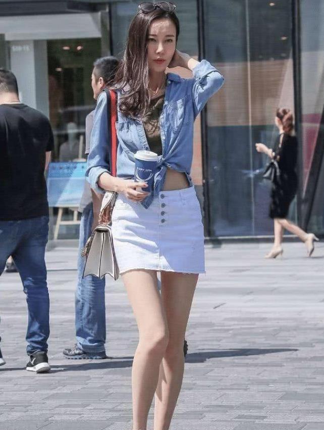 街拍:身材苗条的小姐姐,一件牛仔外套配白色短裙,时尚女神气质
