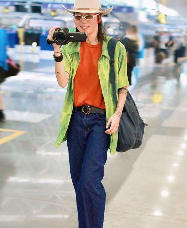 """王菲女儿现身机场,戴墨镜一身""""红配绿"""",反拍摄影师露灿烂微笑"""