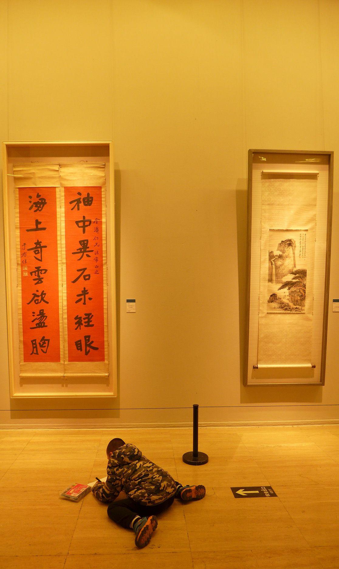 中国美术馆里趴在地上用左手画画的小孩