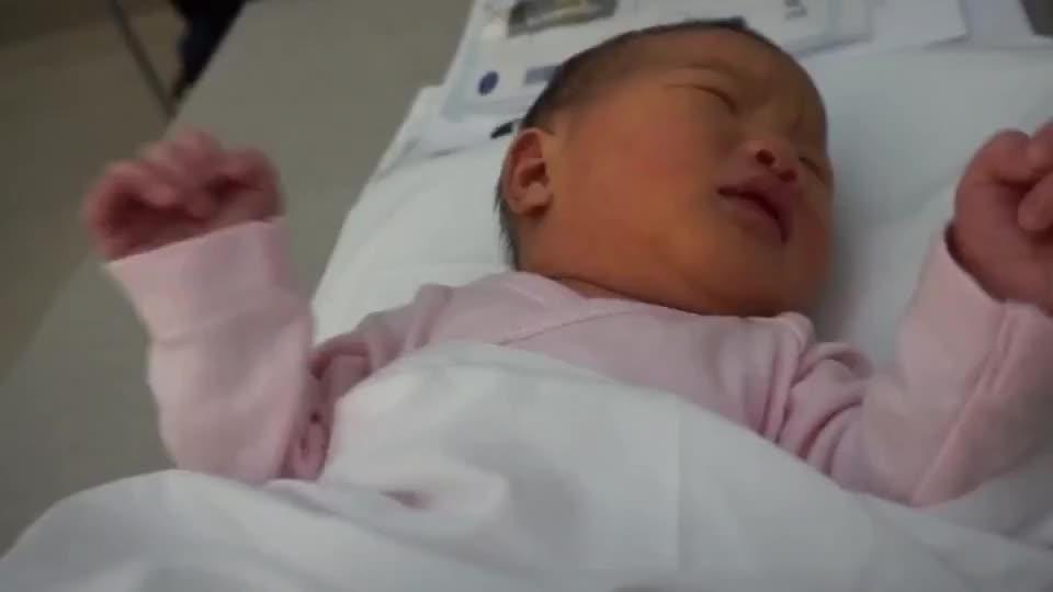 梦中惊醒的宝宝在妈妈安抚下再次睡去 妈妈的手在他身上显得超大