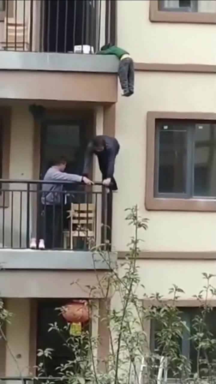 孩子脑袋挂在护栏上 楼下邻居用手托举将其解救