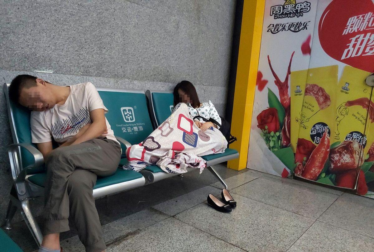 假日旅途画报:旅客在汽车客运站休息椅上晨睡