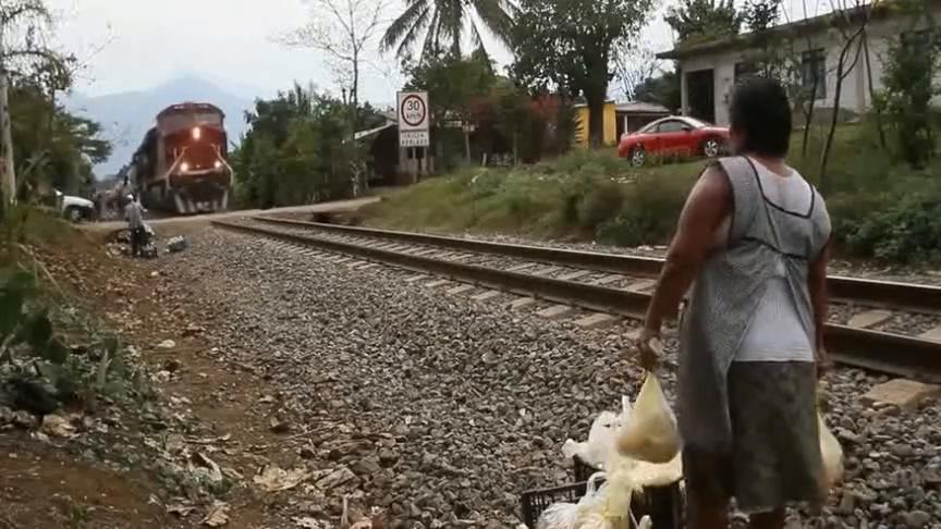 老太太一看就是经常做好事,很容易就把东西扔上行驶的火车!