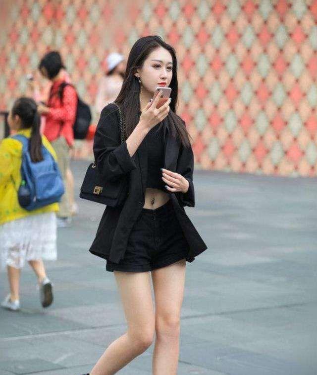 街拍:美女穿黑色上衣,秀出白皙美腿,发型时尚,秀出冷艳女王范