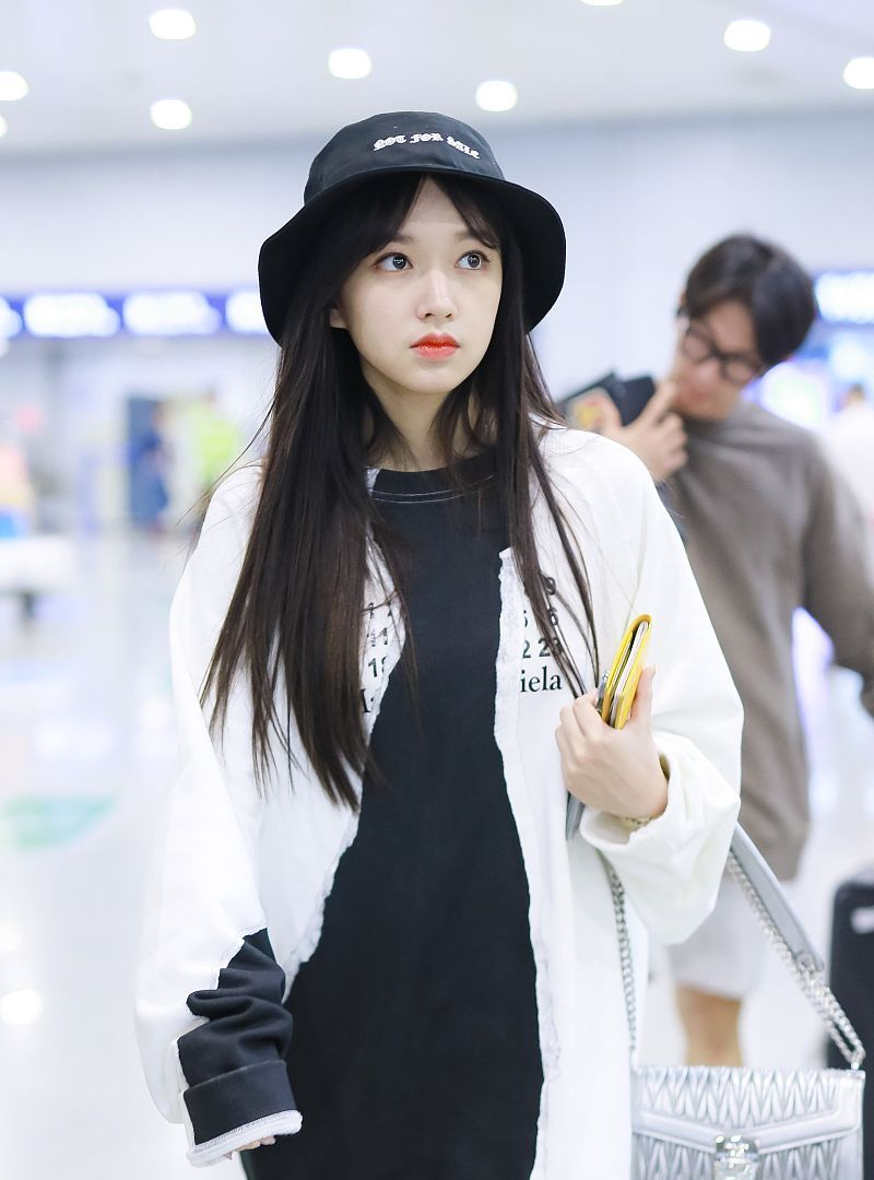 程潇戴帽子妆容精致现身机场,她低头看手机站姿十分霸气