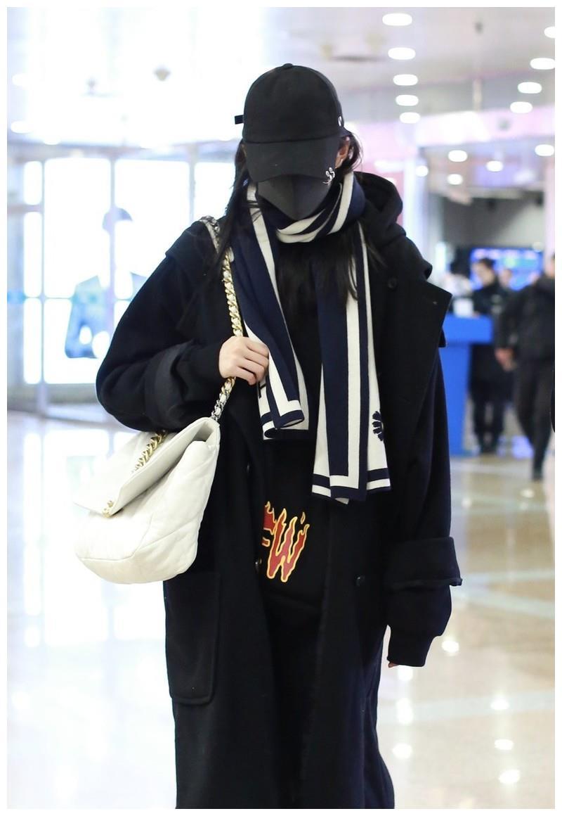 关晓彤低调走机场,黑色大衣配白手袋时尚大气,口罩覆面不敢抬头