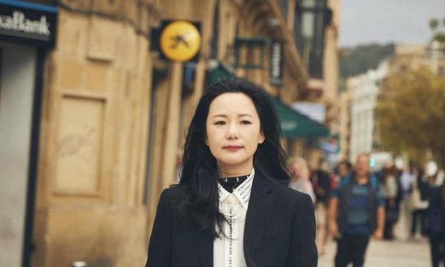 49岁咏梅气质好优雅,穿白衬衫搭配外套现街头,长卷发造型像贵妇
