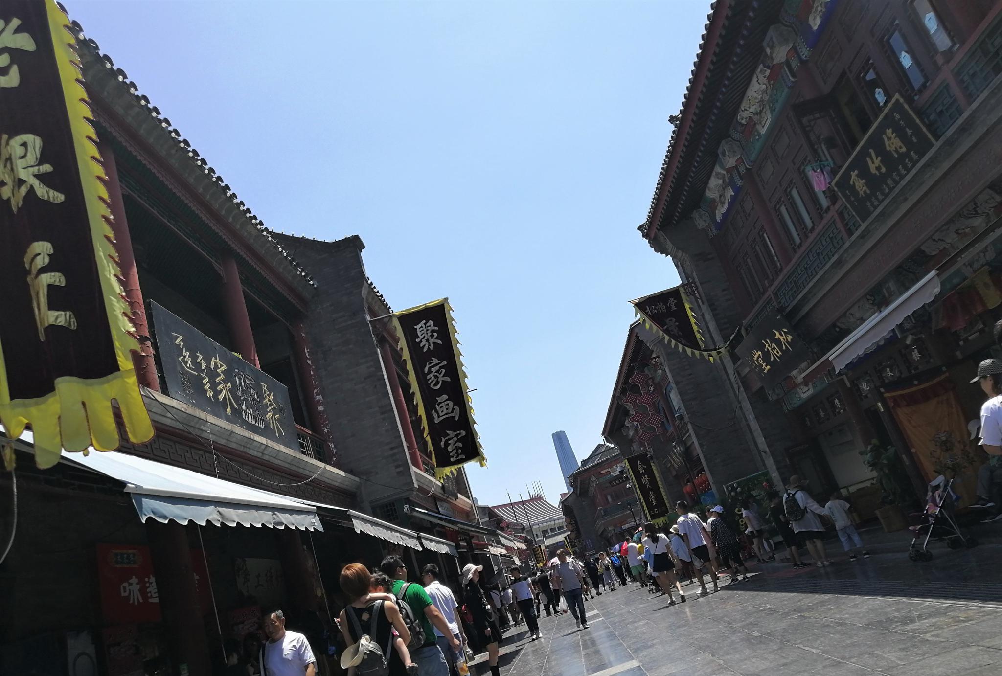 端午节天气炎热,天津古文化街依旧吸引多个旅游团前来打卡
