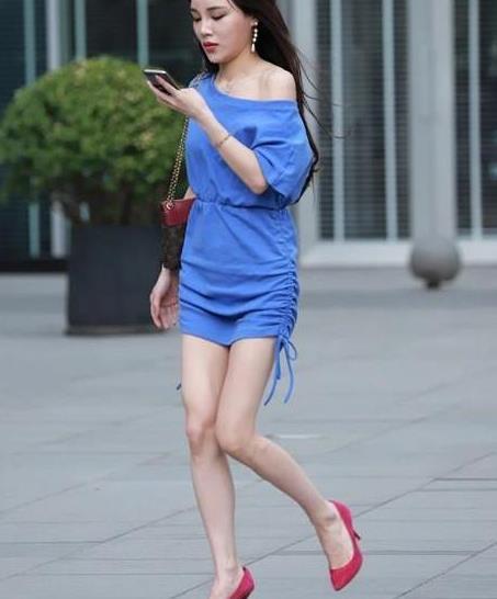 街拍:小姐姐一身蓝色的连衣裙,斜肩的款式很好地展示了个性