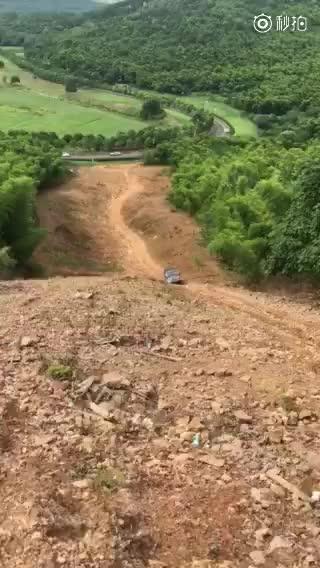 司机开越野车冲高坡失败后连人带车滚下山坡