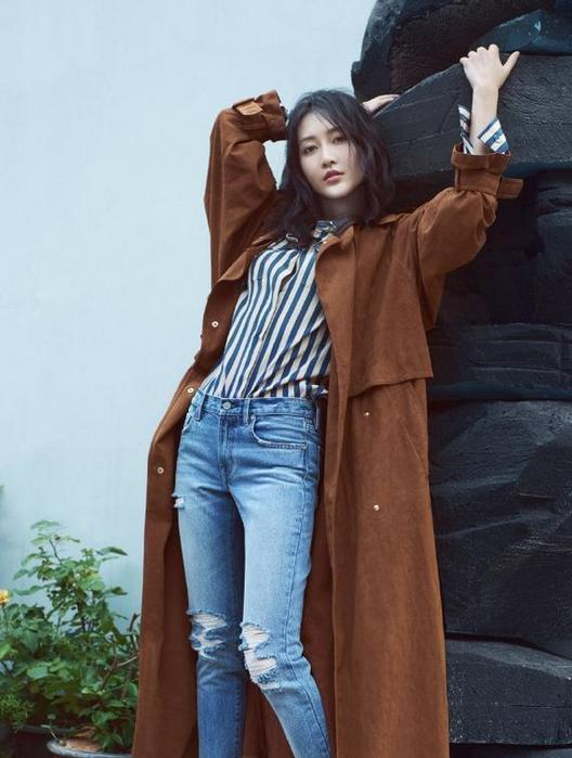 黑白竖条纹衬衫搭配破洞牛仔裤,外搭棕色的长款风衣,凌乱美的发型图片
