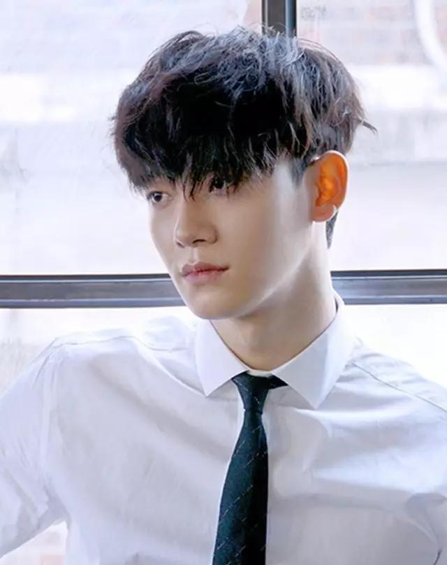 这是一款很适合长相俊秀男生的一款深咖色系的长刘海烫发发型,一张图片