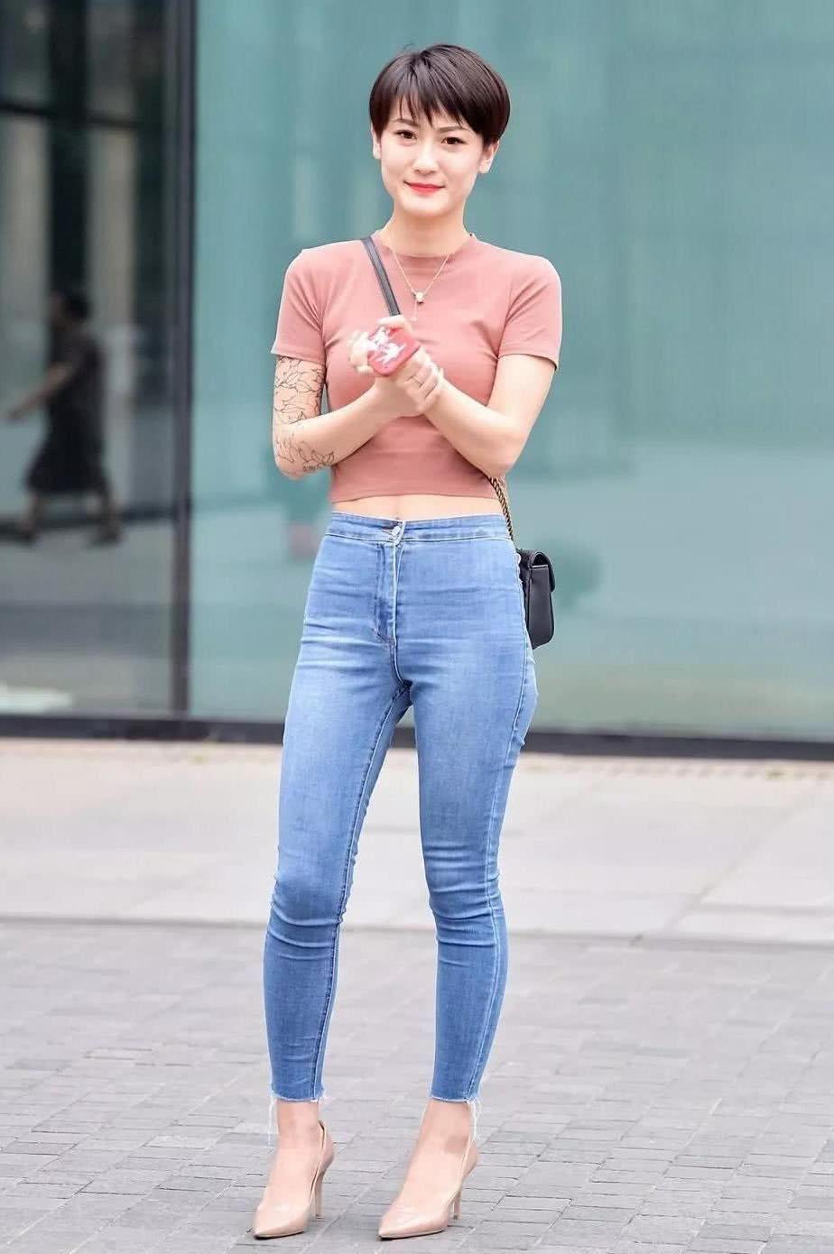 街拍:美女紧身牛仔裤勾勒出平坦健美的蛮腰,清爽的短发干净利落