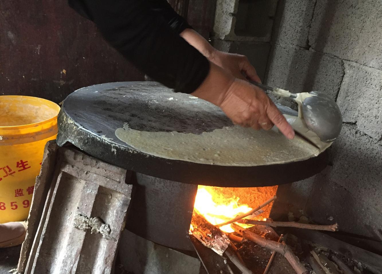 """支起鏊子做煎饼, 鏊子跟前还有一种美食是""""煎饼卷子""""图片"""