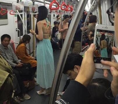 女子地铁上赤裸后背,后背还写着两行字,看清内容人们无法接受