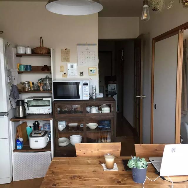 餐桌侧面的橱柜和收纳架上摆放着经常使用的碗碟和家用电器,生活气息