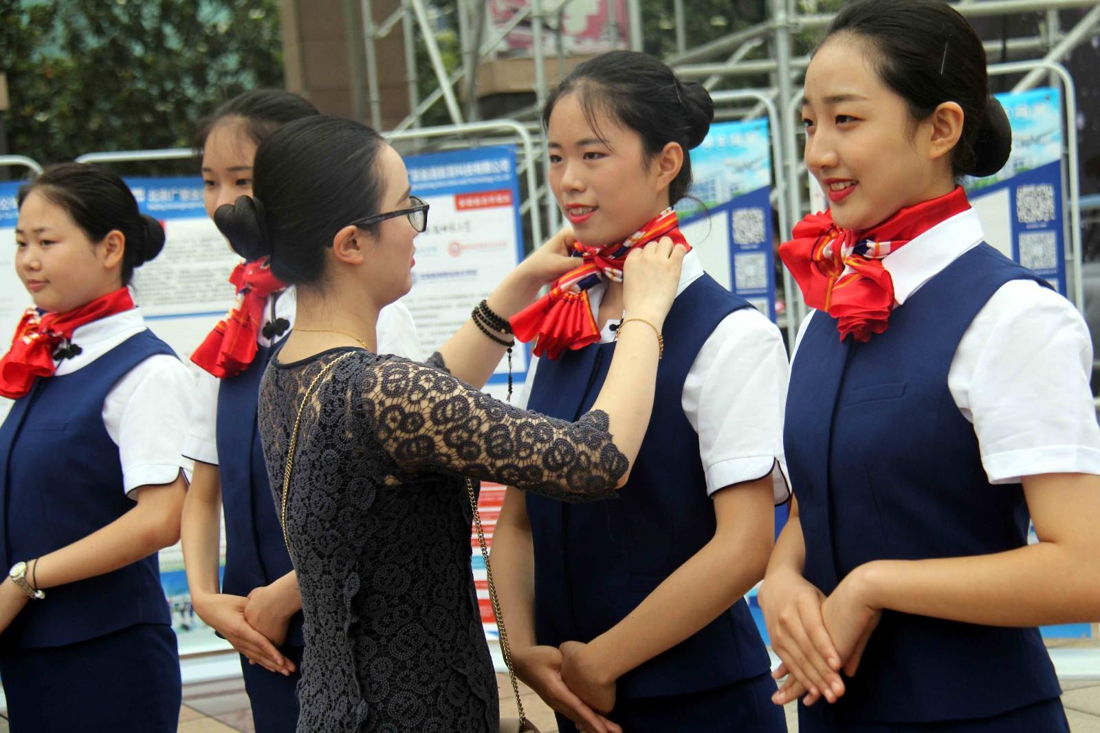 一所中职学校的空乘专业学生们正在老师的指导帮助下,做展示表演前的