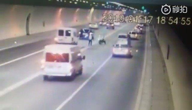 隧道内交警查看路面大坑被后车司机撞翻