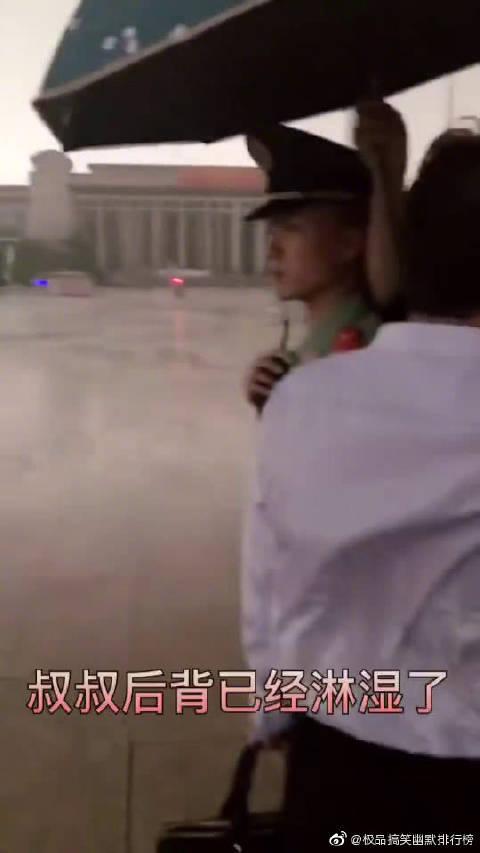 一对老夫妻暴雨中为执勤武警撑伞,为了不让兵哥哥淋到雨