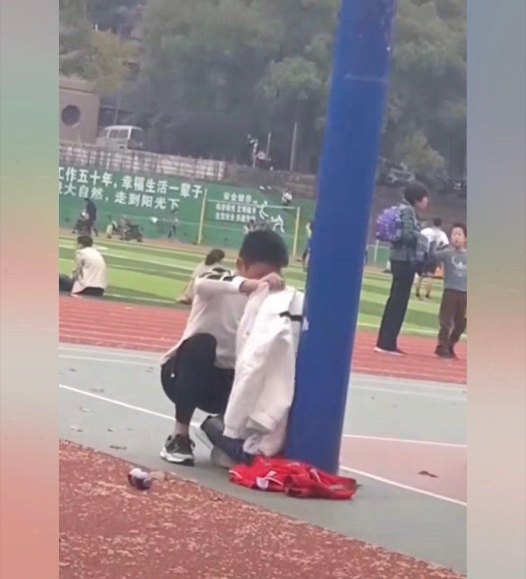 小妹妹在看哥哥打篮球,哥哥怕妹妹着凉,把自己的外套给她披上