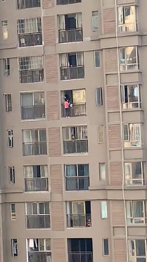 网友爆料,亚太中心附近一栋高楼有人翻出窗外,情况很危险。