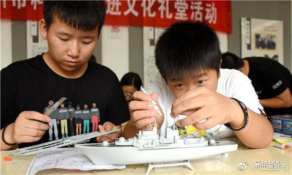 """8月26日,孩子们正在拼装""""杭州号""""现代级导弹驱逐舰模型。当日"""