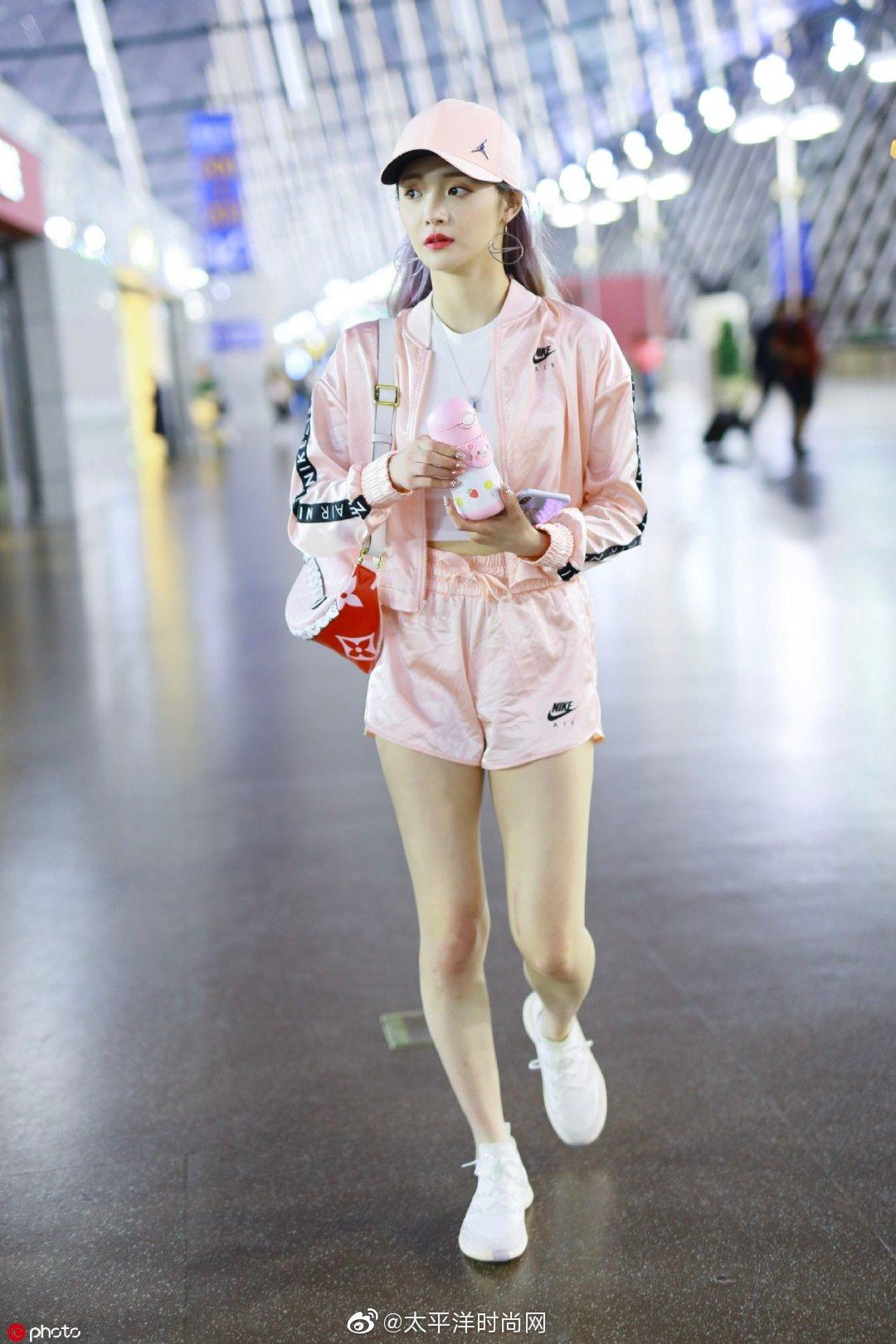 身穿粉色运动套装,内搭白色露脐TEE现身上海机场