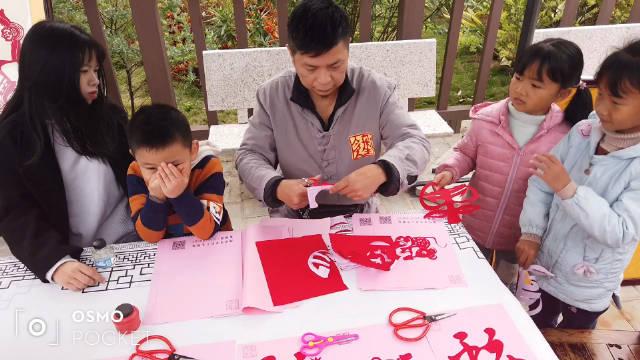 潮州民间艺术表演艺术家表演剪纸艺术,吸引很多小朋友围观